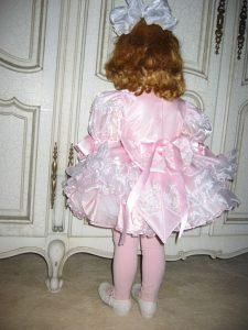 Little girl in fancy pink dress standing in the corner.